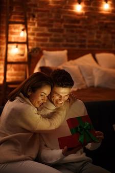 Hübscher mann, der seinem schönen mädchen ein geschenk präsentiert und lächelt