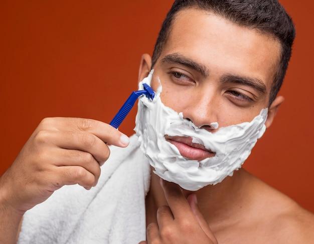 Hübscher mann, der seinen bart mit rasiermesser rasiert