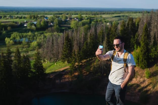 Hübscher mann, der selfie in der natur schießt. wander ausflug. momente des bergsteigens. schießen sie schöne ansichten der waldlandschaften. in einklang mit der natur. sport und spaß im freien