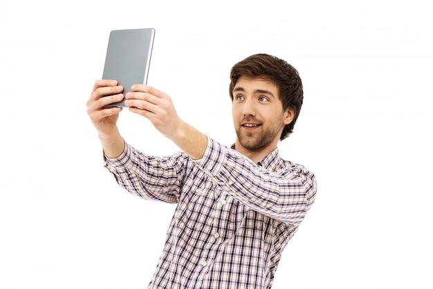 Hübscher mann, der selfie mit digitalem tablett nimmt