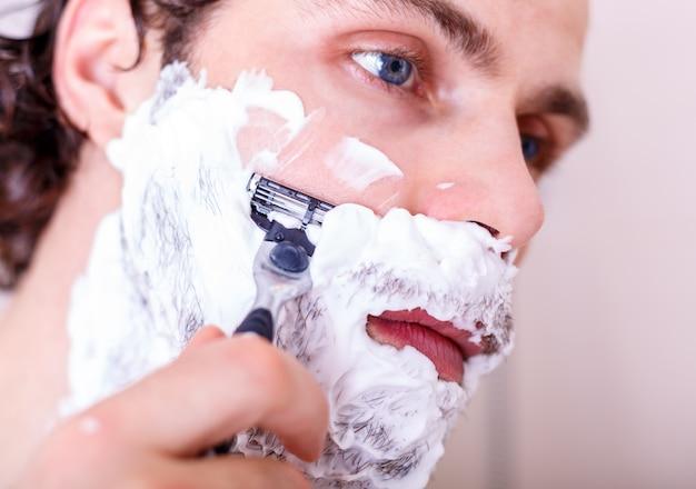 Hübscher mann, der sich im badezimmer rasiert