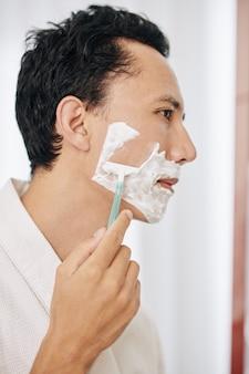 Hübscher mann, der sich rasiert