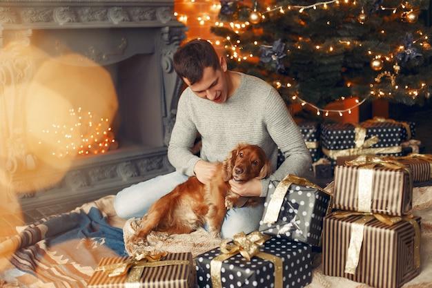Hübscher mann, der sitzt, hört kamin mit einem hund
