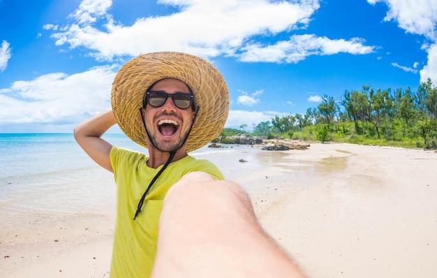 Hübscher mann, der spaß hat, ein selfie auf der tropischen insel im urlaub zu nehmen