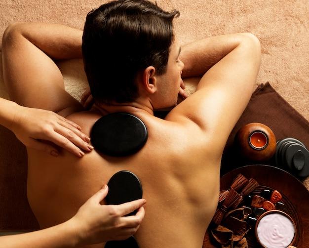 Hübscher mann, der steinmassage im spa-salon hat. gesunder lebensstil.