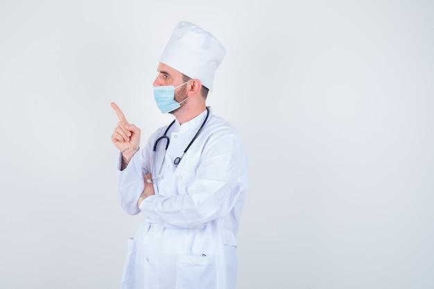 Hübscher mann, der stethoskop um hals hält, links im weißen medizinischen laborkittel, in der maske zeigt und zuversichtlich schaut. vorderansicht.