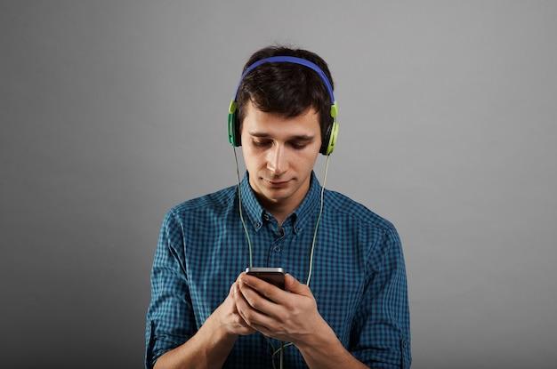 Hübscher mann, der telefon verwendet, um musik in kopfhörern zu hören