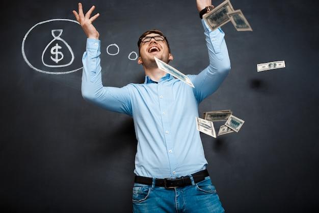 Hübscher mann, der über tafel mit gezeichnetem dollarkonzept steht
