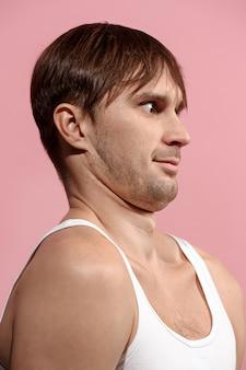 Hübscher mann, der überrascht auf rosa lokalisiert schaut