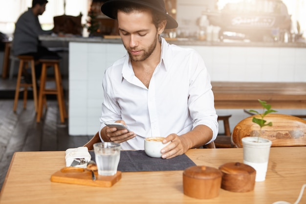 Hübscher mann, der weißes hemd und schwarzen stilvollen hut trägt, der drahtlose internetverbindung auf seinem handy verwendet, freunde online über soziale netzwerke mitteilt, während er am tisch im gemütlichen café sitzt