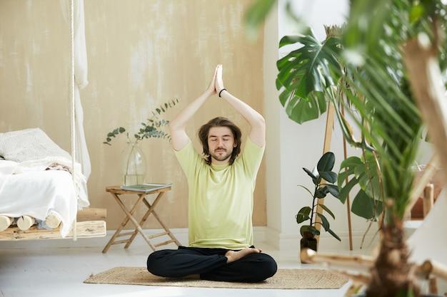 Hübscher mann, der yoga zu hause praktiziert, erwachsener, der yoga-asana tut, die im lotus-asana sitzt, achtsamkeitskonzept