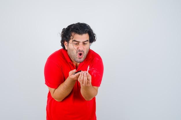 Hübscher mann, der zigarette hält, es im roten t-shirt betrachtet und fokussierte vorderansicht schaut.