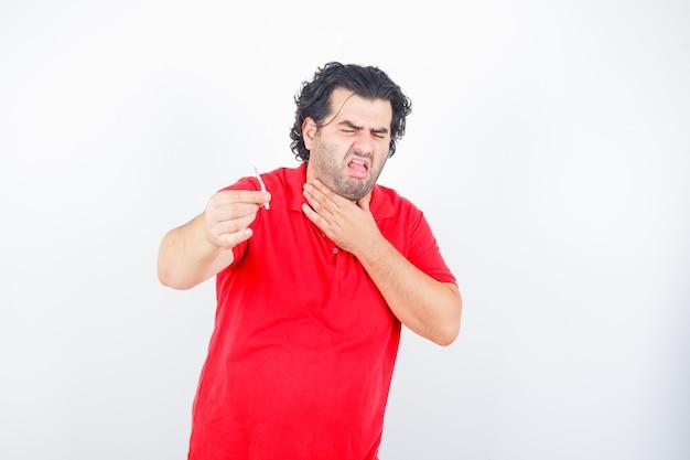 Hübscher mann, der zigarette hält, hand am hals hält, im roten t-shirt hustet und unzufrieden aussieht, vorderansicht.