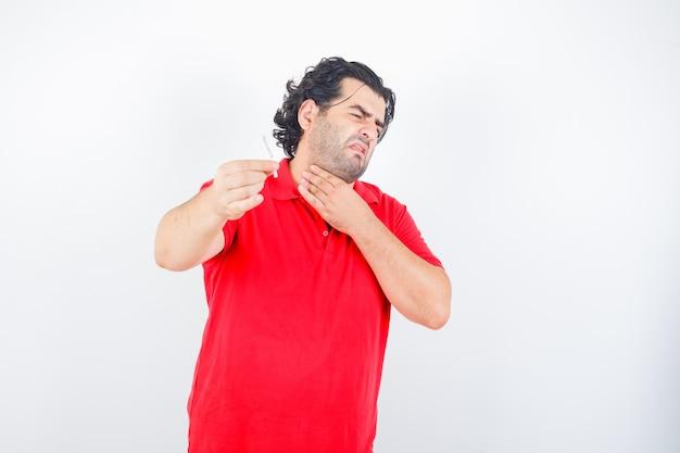 Hübscher mann, der zigarette hält, hand am hals im roten t-shirt hält und unzufrieden schaut, vorderansicht.