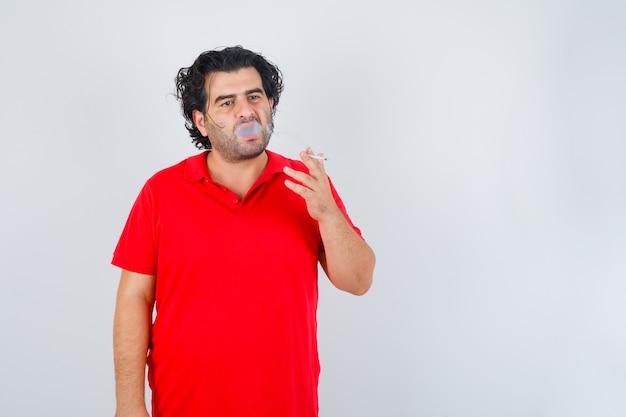 Hübscher mann, der zigarette im roten t-shirt raucht und ernst schaut. vorderansicht.