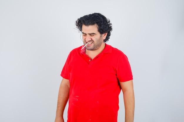 Hübscher mann, der zigarette im roten t-shirt raucht und genervt schaut. vorderansicht.