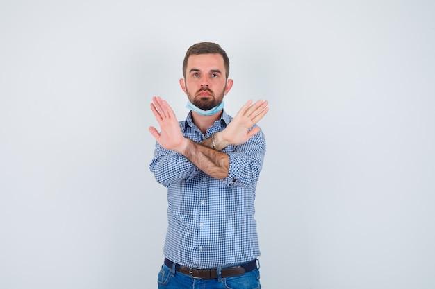 Hübscher mann, der zwei arme verschränkt hält und kein zeichen gestikuliert, während er maske unter kinn in hemd, jeans, maske hält und ernst aussieht. vorderansicht.