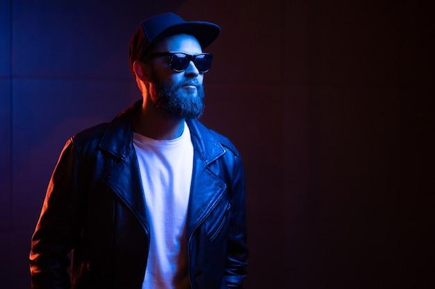 Hübscher mann des hipsters auf den straßen der stadt, die durch leuchtreklamen beleuchtet werden. er trägt eine leder-bikerjacke oder eine asymmetrische reißverschlussjacke mit schwarzer mütze, jeans und sonnenbrille.
