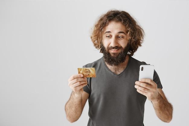 Hübscher mann des nahen ostens, der online einkauft und kreditkarte und handy hält