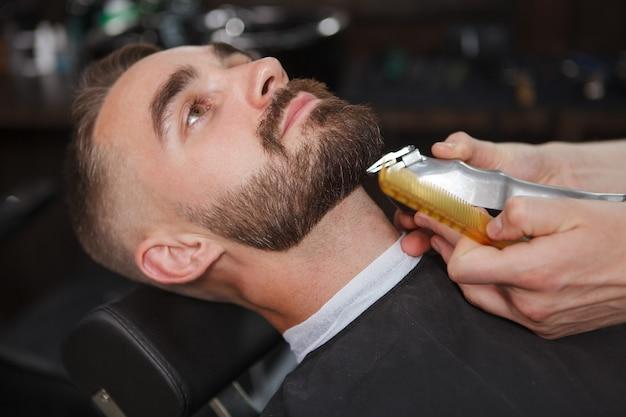 Hübscher mann entspannte sich in einem friseurladen