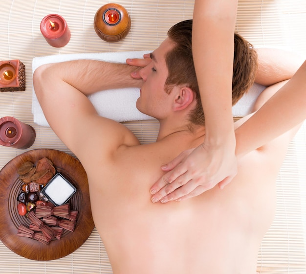 Hübscher mann entspannte sich und genoss eine tiefenmassage im spa-salon.