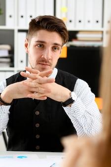 Hübscher mann im anzug bietet vertragsform auf zwischenablageblock und silberstiftporträt.