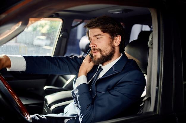 Hübscher mann im anzug, der ein auto fährt und am telefon spricht