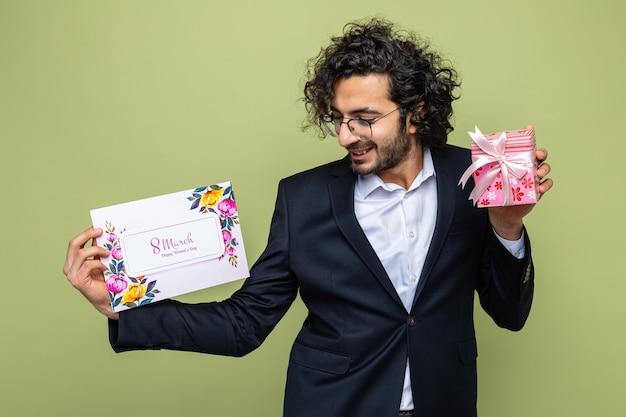 Hübscher mann im anzug, der grußkarte und geschenk hält, das glückliches und positives lächeln der karte betrachtet, das fröhlich den internationalen frauentag 8. märz über grünem hintergrund feiert