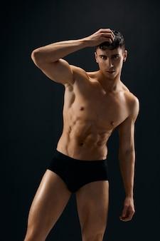Hübscher mann im dunklen höschen muskulöses studiomodell.