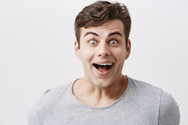 Hübscher mann im grauen t-shirt, lächelt vor überraschung, sieht mit abgehörten blauen augen aus und ist erstaunt, unerwartete nachrichten zu hören oder geschenk von freund zu sehen. positives emotions- und gefühlskonzept.