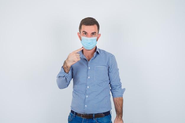 Hübscher mann im hemd, in der jeans, in der maske, die mit zeigefinger auf sich selbst zeigt und ernst schaut, vorderansicht.