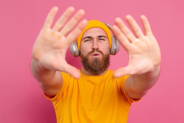 Hübscher mann im lässigen hören der musik mit kopfhörern lokalisiert auf rosa hintergrund