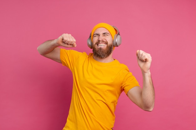 Hübscher mann im lässigen tanzen mit kopfhörern lokalisiert auf rosa hintergrund