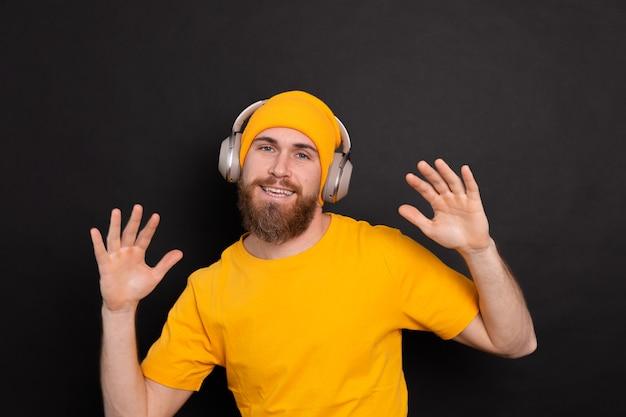 Hübscher mann im lässigen tanzen mit kopfhörern lokalisiert auf schwarzem hintergrund