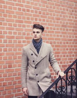 Hübscher mann im mantel nahe ziegelmauer