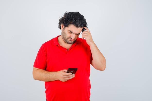 Hübscher mann im roten t-shirt, das telefon hält, kopf kratzt und fokussiert, vorderansicht schaut.