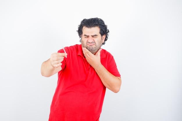Hübscher mann im roten t-shirt, das zigarette hält, hand am hals hält, verzieht das gesicht und sieht unzufrieden aus, vorderansicht.