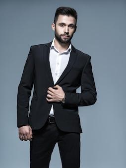 Hübscher mann im schwarzen anzug mit weißem hemd, der attraktiven kerl mit modefrisur aufwirft. selbstbewusster mann mit kurzem bart. erwachsener junge mit braunen haaren. volles porträt.