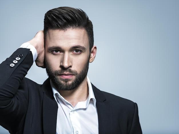 Hübscher mann im schwarzen anzug mit weißem hemd, der attraktiven kerl mit modefrisur aufwirft. selbstbewusster mann mit kurzem bart. erwachsener junge mit braunen haaren.