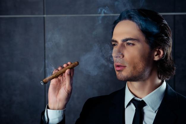 Hübscher mann im schwarzen smoking, der zigarre mit rauch hält