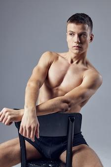 Hübscher mann im sportlichen körperbau der schwarzen shorts sitzt auf einem stuhl, der aufwirft