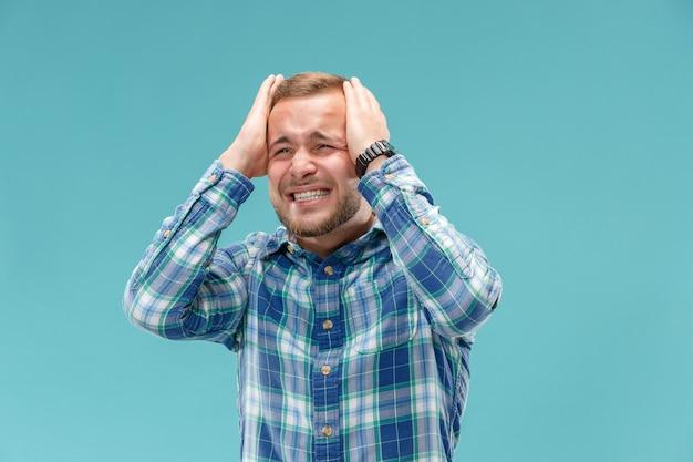 Hübscher mann im stress lokalisiert auf blau
