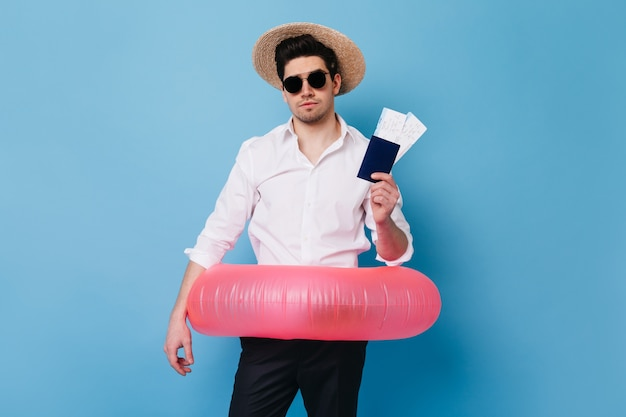 Hübscher mann im strohhut zeigt pass und flugtickets. porträt des kerls in der geschäftskleidung, die aufblasbaren kreis hält.