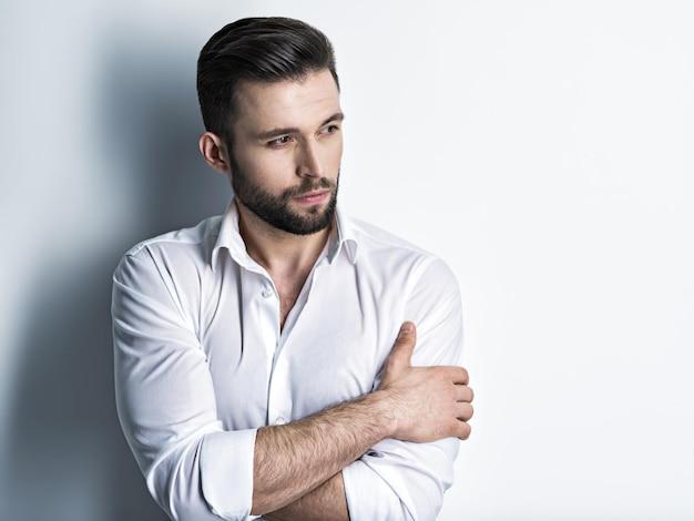 Hübscher mann im weißen hemd, posierend. attraktiver typ mit modefrisur. selbstbewusster mann mit kurzem bart. erwachsener junge mit braunen haaren. nahaufnahmeporträt.
