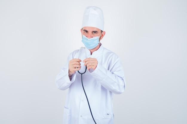 Hübscher mann im weißen medizinischen laborkittel, maske, die stethoskop hält und selbstbewusst, vorderansicht schaut.