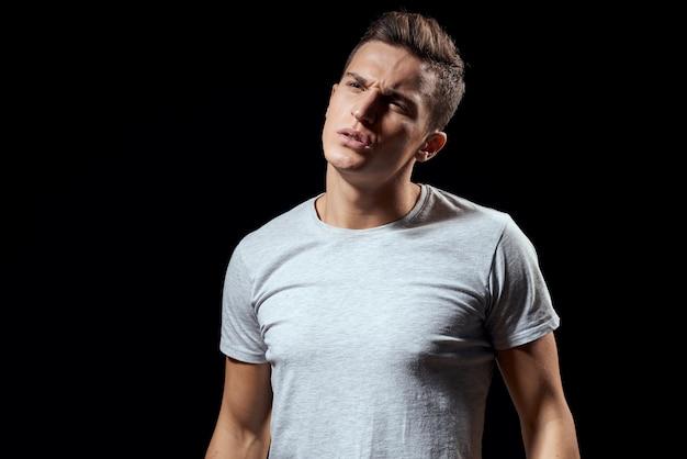 Hübscher mann im weißen t-shirt auf schwarz