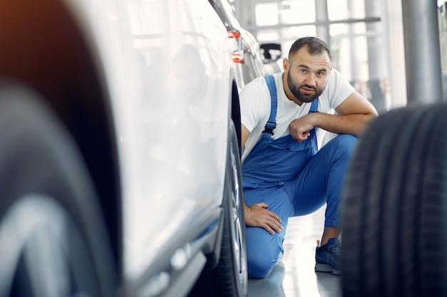 Hübscher mann in blauer uniform überprüft das auto