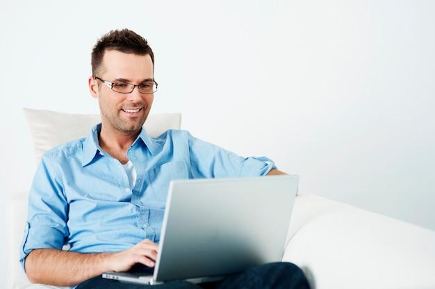 Hübscher mann in den gläsern, die laptop auf sofa verwenden