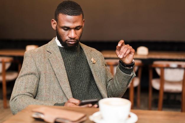 Hübscher mann in der grauen jacke, die neben einem tisch sitzt