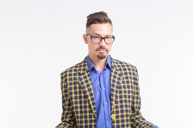 Hübscher mann in der jacke mit bart und schnurrbart in den gläsern, die über weißem hintergrund stehen